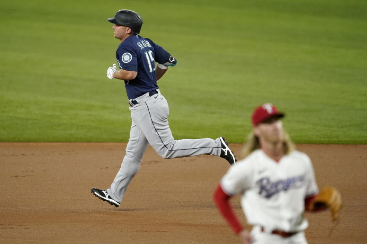 Seattle Mariners' Kyle Seager, rear, rounds the bases after hitting a two-run home run on a pitch from Texas Rangers starting pitcher Mike Foltynewicz, front, in the first inning of a baseball game in Arlington, Texas, Wednesday, Aug. 18, 2021.