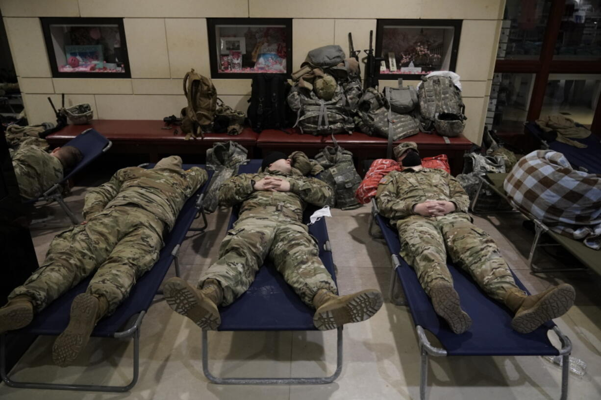 FILE - In this Jan. 18, 2021, file photo National Guard troops sleep inside the Capitol Visitor's Center at the Capitol in Washington. Over the past year, National Guard members have been called in to battle the COVID-19 pandemic, natural disasters and race riots. (AP Photo/J.