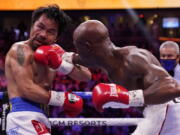Manny Pacquiao, left, of the Philippines, is hit Yordenis Ugas, of Cuba, in a welterweight championship boxing match Saturday, Aug. 21, 2021, in Las Vegas.