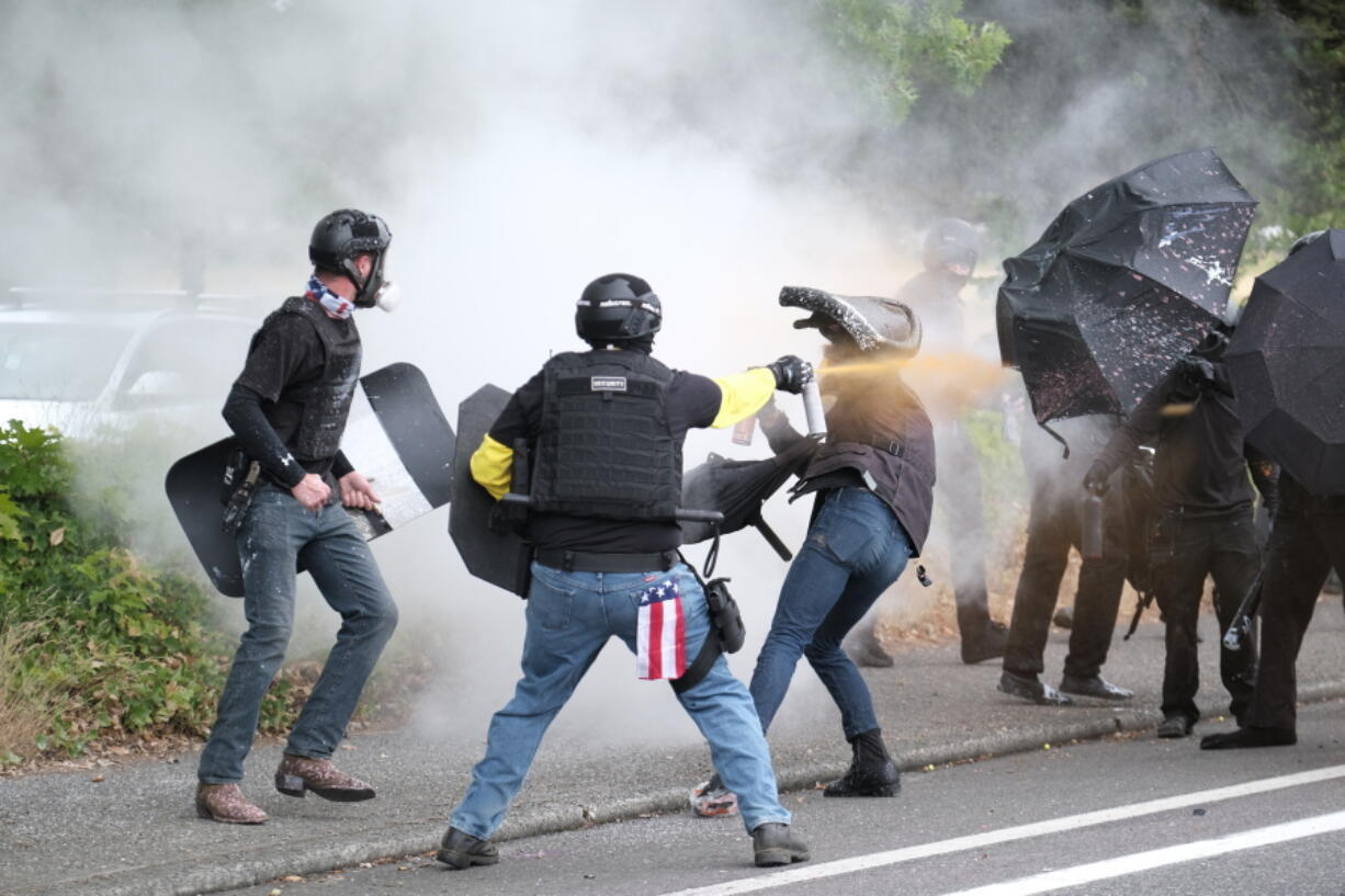This Sunday, Aug. 22, 2021 photo, members of the far-right group Proud Boys and anti-fascist protesters spray bear mace at each other during clashes between the politically opposed groups in Portland, Ore.  Police in Portland have been criticized that they did little to prevent violent clashes between right- and left-wing protesters on Sunday.