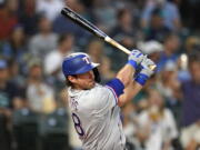 Texas Rangers' DJ Peters drives watches his RBI double against the Seattle Mariners during the fifth inning of a baseball game Tuesday, Aug. 10, 2021, in Seattle.