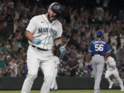 Seattle Mariners' Luis Torrens, left, celebrates his single that scored Jarred Kelenic with the winning run off of Texas Rangers pitcher Dennis Santana (56) during the ninth inning of a baseball game Wednesday, Aug. 11, 2021, in Seattle. The Mariners won 2-1. (AP Photo/Ted S.
