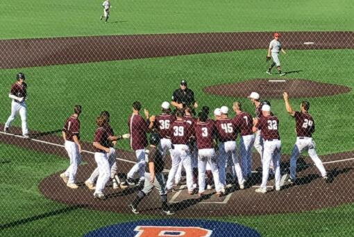 The Ridgefield Raptors await John Peck at home plate after his game-winning home run in the 11th inning against the Walla Walla Sweets on Sunday at Ridgefield Outdoor Recreation Complex.