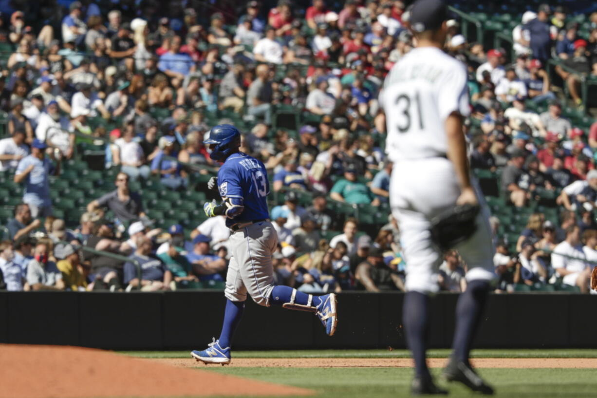 Kansas City Royals' Salvador Perez rounds third after hitting a two-run home run as Seattle Mariners starting pitcher Tyler Anderson looks on during the fifth inning of a baseball game Saturday, Aug. 28, 2021, in Seattle.