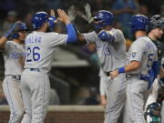 Kansas City Royals' Salvador Perez (13) is greeted at the plate by Emmanuel Rivera (26) after Perez hit a grand slam against the Seattle Mariners during the sixth inning of a baseball game Thursday, Aug. 26, 2021, in Seattle. (AP Photo/Ted S.