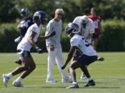 Seattle Seahawks head coach Pete Carroll, center, watches as cornerback Ahkello Witherspoon, left, runs a drill with cornerback Bryan Mills, right, during NFL football practice Thursday, July 29, 2021, in Renton, Wash. (AP Photo/Ted S.