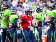 Seattle Seahawks quarterback Russell Wilson (3) greets the defense before playing a mock game as part of an NFL football training camp at Lumen Field in Seattle, Sunday, Aug. 8, 2021.