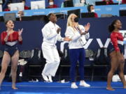 FILE - In this July 27m 2021 file photos, gymnasts from the United States, Simone Biles, center, Jordan Chiles , right, and Sunisa Lee cheer Grace McCallum as she performs on the floor during the artistic gymnastics women's final at the 2020 Summer Olympics, in Tokyo. Biles and Naomi Osaka are prominent young Black women under the pressure of a global Olympic spotlight that few human beings ever face. But being a young Black woman -- which, in American life, comes with its own built-in pressure to perform -- entails much more than meets the eye.