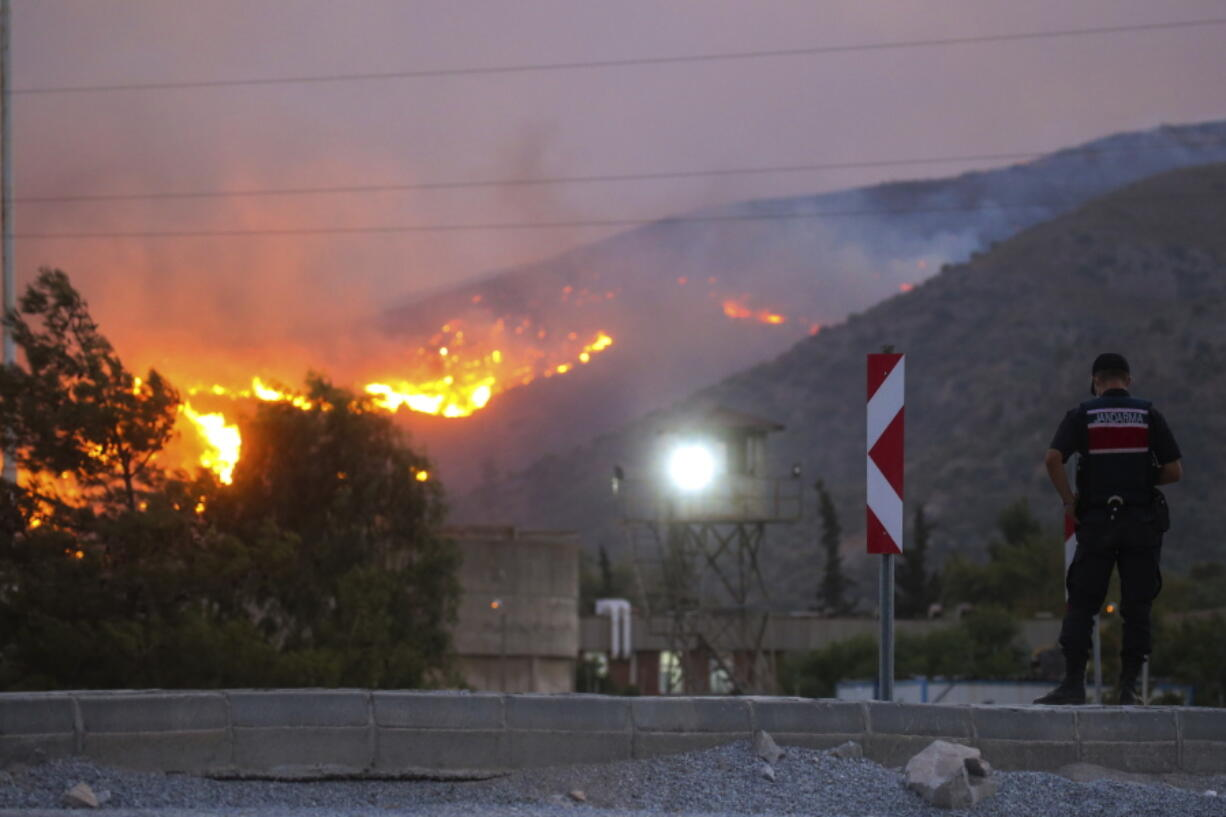 A paramilitary police officer stands close to Kemerkoy Thermal Power Plant, right, with the blaze approaching in the background, in Milas, Mugla, Turkey, Tuesday, Aug. 3, 2021. Turkish President Recep Tayyip Erdogan's government is facing increased criticism over its apparent poor response and inadequate preparedness for large-scale wildfires that have left eight people dead and forced thousands to flee their homes.