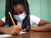 """Sixth-grader Adriana Campbell, 11, jots down her name as she starts to work on her first assignment during the first day of school on Wednesday, Aug. 4, 2021 at Freeman Elementary School in Flint, Mich. """" Schools have begun reopening in the U.S. with most states leaving it up to local schools to decide whether to require masks."""