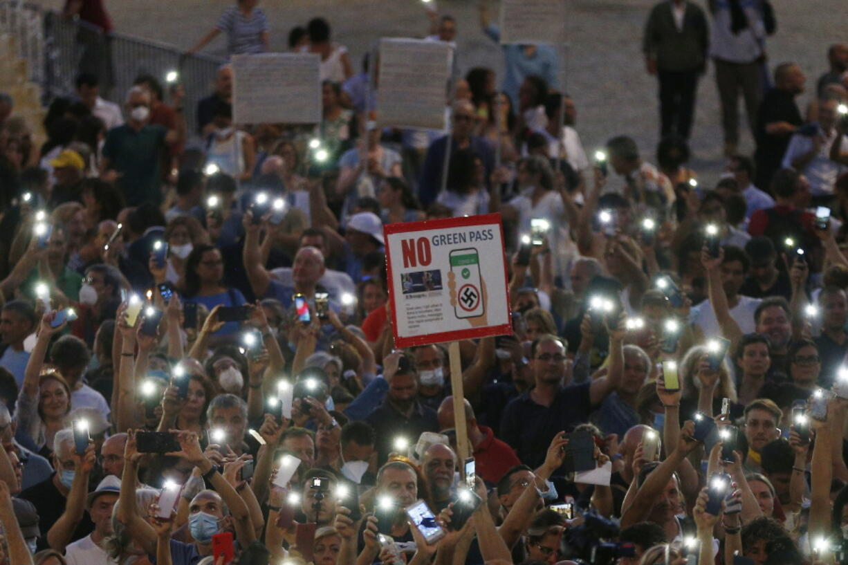 """FILE - In this  Wednesday, July 28, 2021 file photo, people stage a protest against the COVID-19 vaccination pass in Rome. Shouts of """"liberty"""" have echoed through Italian and French streets and squares as thousands show their opposition to plans to require vaccination cards to continue normal social activities, like dining indoors at restaurants, visiting museums or cheering home teams in stadiums."""