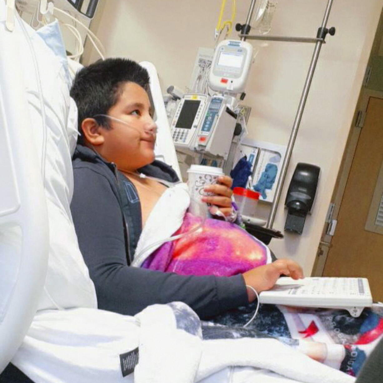 This 2021 photo provided by Yessica Gonzalez shows her son, Francisco Rosales, 9, in the intensive care unit at Children's Medical Center in Dallas, Texas. The day before he was supposed to start fourth grade, Francisco was admitted to the hospital due to severe COVID-19, struggling to breathe, with dangerously low oxygen levels and an uncertain outcome.
