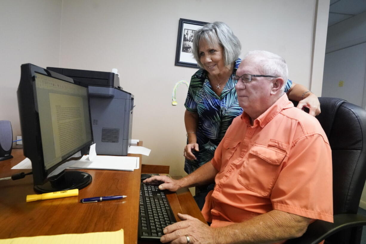 Roger West, right, columnist of the Westside Journal in northeast Florida, looks over news copy with his wife Dawn, owner and publisher, in the newspaper office Tuesday, Aug. 10, 2021, in Callahan, Fla. Outspoken as he had been in opposing COVID-19 vaccines he reconsidered after the virus returned with a deadly vengeance in mid-July.
