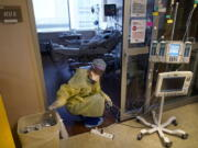 Jodie Ford, an ICU nurse, moves electrical cords for medical machines, outside the room of a patient suffering from COVID-19, in an intensive care unit at the Willis-Knighton Medical Center in Shreveport, La., Tuesday, Aug. 17, 2021.