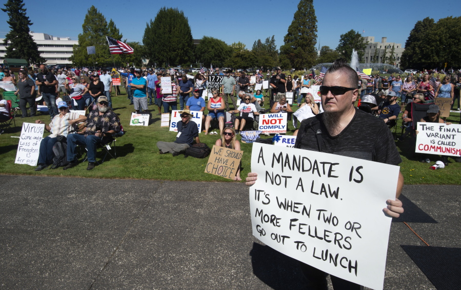 Olympia resident and state employee William Baker along with concerned citizens gather outside the Capitol to protest Gov. Jay Inslee's vaccine mandate for state workers, Saturday, Aug. 28, 2021 in Olympia, Wash.