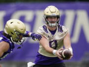 Washington Huskies quarterback Dylan Morris hands-off the ball during an NCAA college football team practice Friday, Aug. 6, 2021, in Seattle.