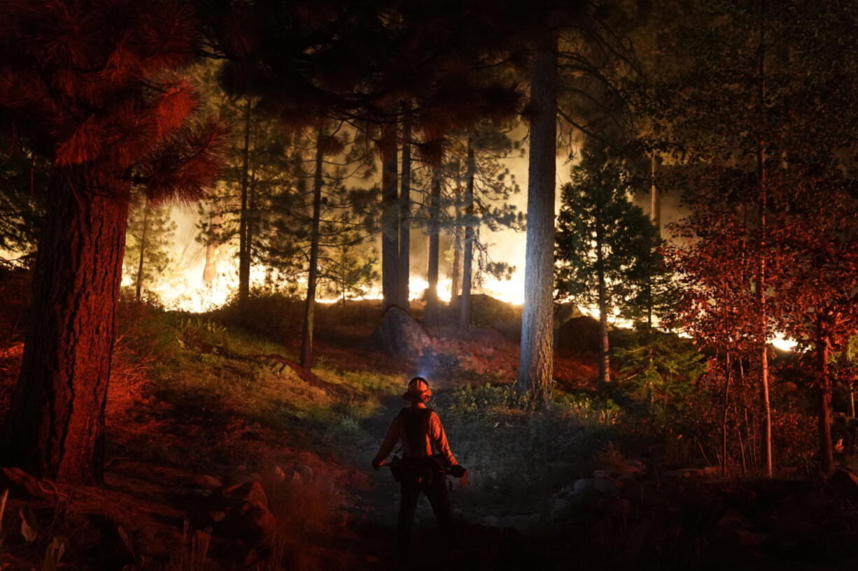 A firefighter monitors the Caldor Fire burning near homes in South Lake Tahoe, Calif., Monday, Aug. 30, 2021. As the winds returned this week, the Caldor Fire roared over the Sierra crest and bore down on the southern end of Lake Tahoe. (AP Photo/Jae C.