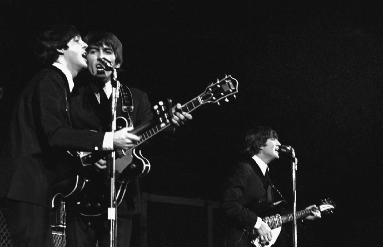 The Beatles' Paul McCartney and George Harrison in concert in America in 1964.