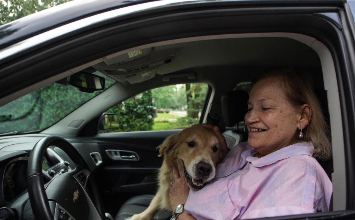 Margie Bauer of Harper Woods, Mich., cuddles her dog Liberty inside her 2015 Chevy Equinox on Aug. 22. Bauer bought the vehicle because two dogs could easily fit in the back seat.