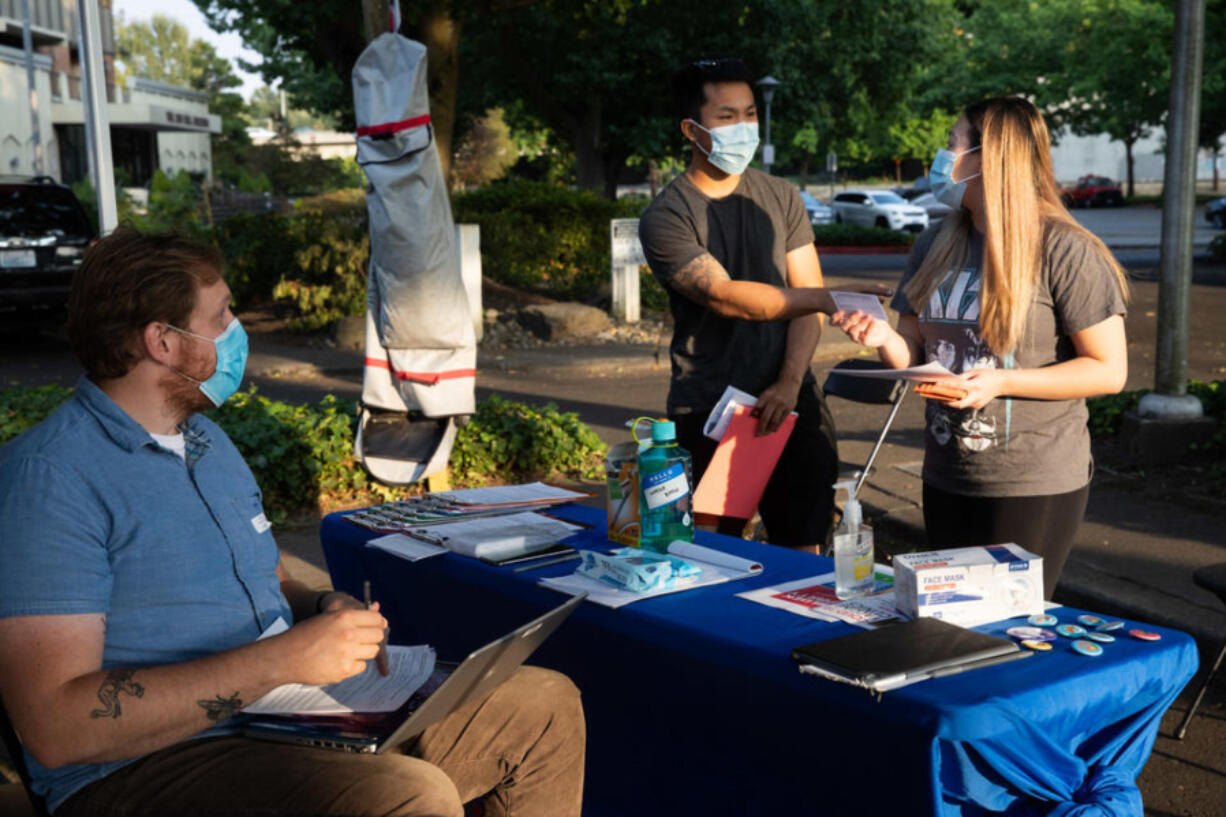 Michael Chu and Sandy Nguyen of Renton visit a King County Public Health pop-up vaccination site together for a vaccine at Renton Library on Aug. 25, 2021. (Matt M.