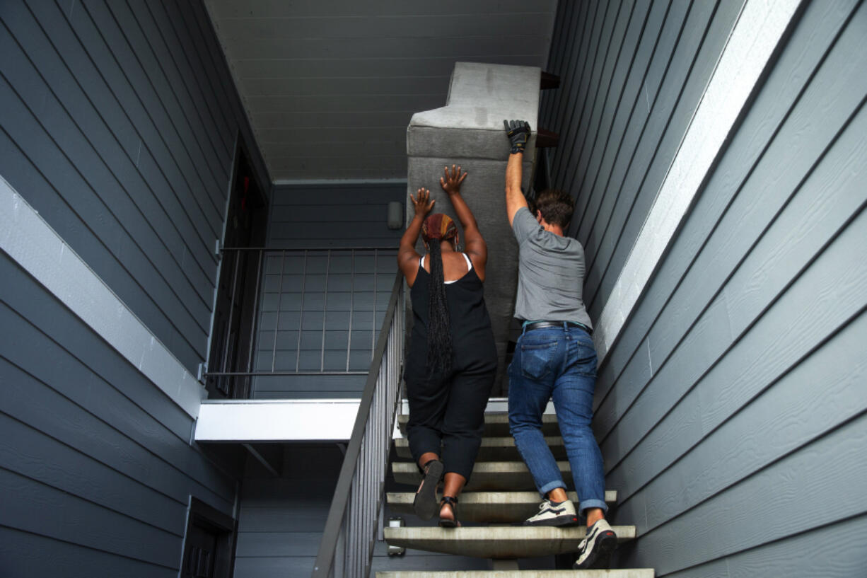 Haley Cummins, housing coordinator, left, and Elijah Knepper, gift-in-kind coordinator for local nonprofit World Relief, heave a large donated sofa up the stairs into a new apartment for a family recently resettled from Kenya to South King County. Housing affordability is a major limiting factor for new refugees arriving to the Seattle area, as well as finding scarce 3-4 bedroom apartments for large families.