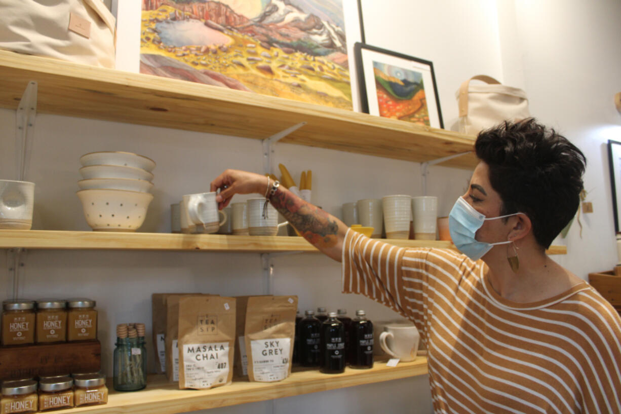 Lori Cano, owner of the new Poppy & Hawk retail shop in downtown Camas, straightens a stoneware coffee mug crafted by Hanselmann Pottery, a studio out of Corrales, N.M., on Aug. 26.