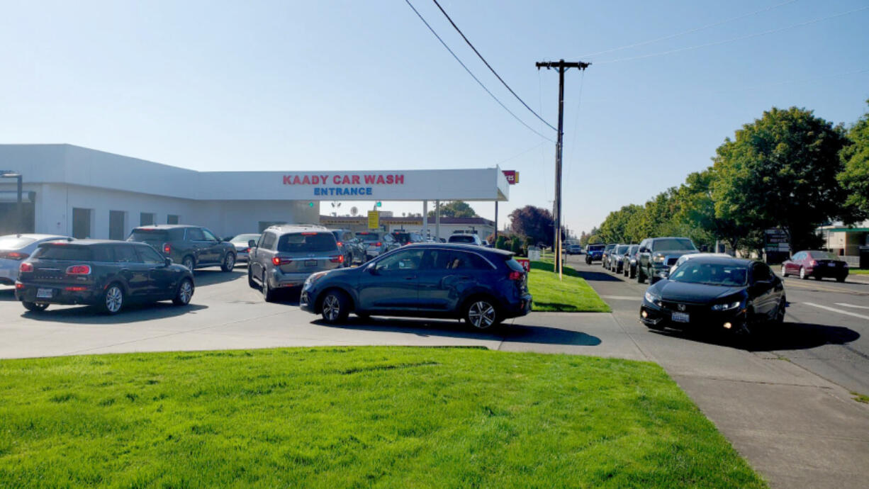 The line at Kaady Car Wash backed up on Mill Plain Boulevard on Wednesday morning after people awoke to their cars covered in ash from early-morning rainfall.