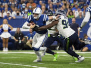 Indianapolis Colts quarterback Carson Wentz (2) scrambles from pressure by Seattle Seahawks defensive end Rasheem Green (94) during the season opener on Sunday, Sept. 12, 2021, in Indianapolis. Green had perhaps his best day as a pro with four tackles, a sack and two pass breakups.