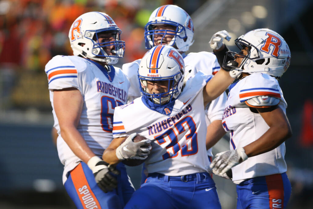 Ridgefield Spudders Davis Pankow (33) celebrates a first half score with teammates in the first half against the Hockinson Hawks in the 2A Greater St. Helens League season opener for both teams at Hockinson High School on Friday, Sept. 17, 2021. (Randy L.