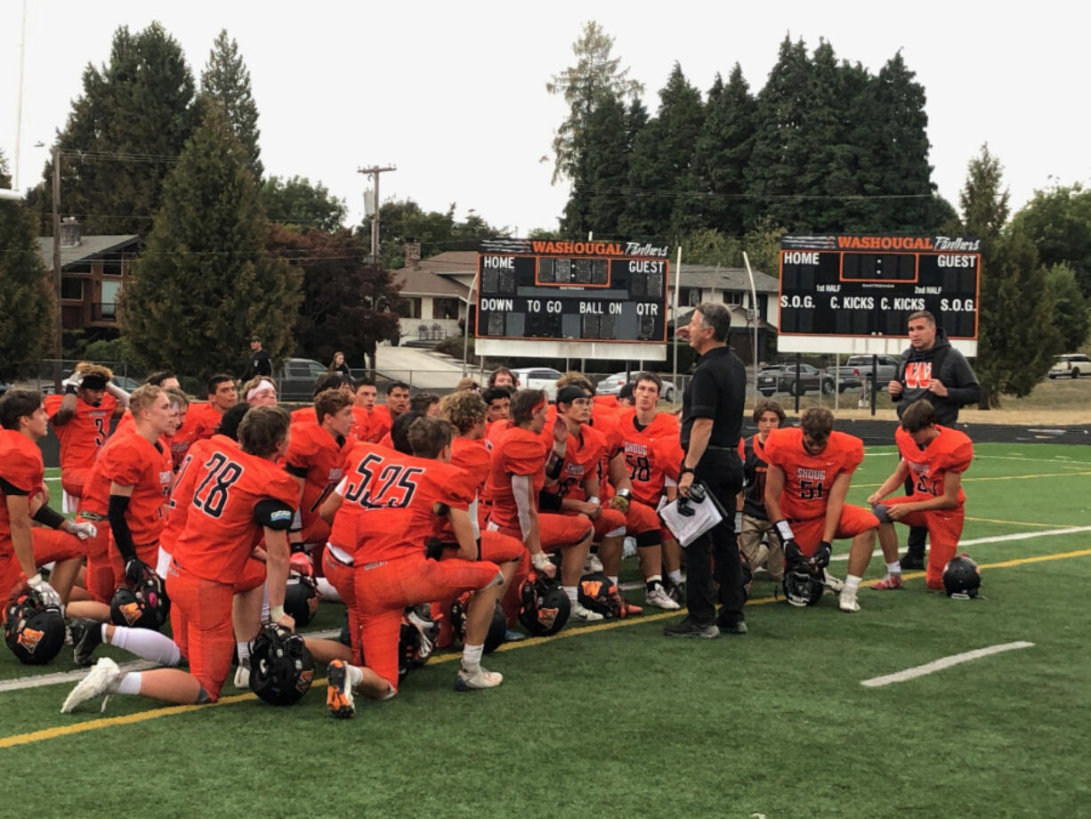 Washougal football coach Dave Hajek talks to his team after a 41-0 win over Woodland on Friday at Fishback Stadium.