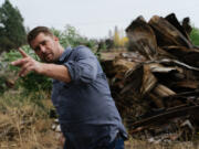 Scott Hokonson, Director of Long Term Recovery in Malden, Wash., points out remaining damage and debris left in the town. The high cost of cleanup and removal of debris has played a large part in the delay of rebuilding.