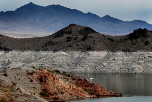 """A boat navigates Lake Mead, where a white """"bathtub ring"""" along the shore shows how far below capacity the nation's largest reservoir is on April 1, 2021. Water levels at Lake Mead hit their lowest point in history amid an ongoing megadrought, creating uncertainty about the water supply for millions in the Western U.S."""