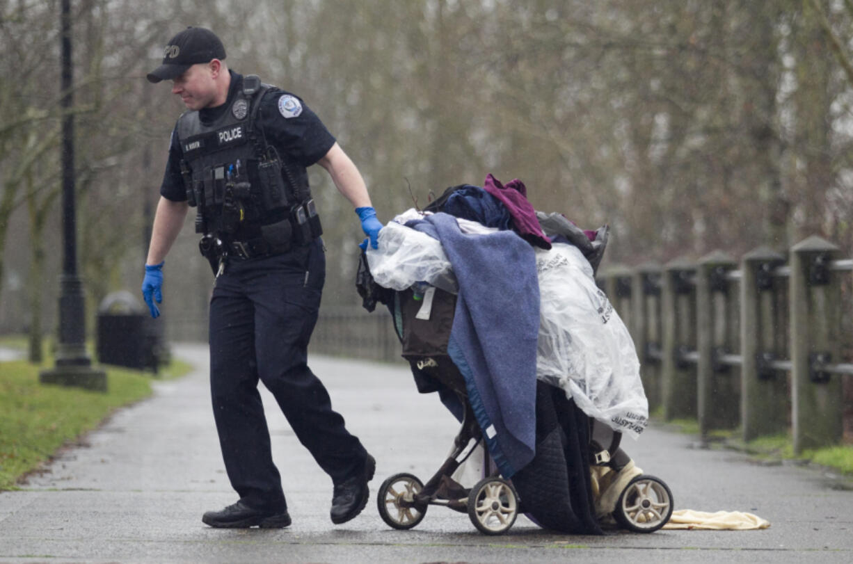 """Officer Brian Ruder hauls away a load of debris left by houseless people along the Columbia River in 2015. The Vancouver City Council passed an ordinance Monday night allowing camping during the day for nighttime-working houseless people, and also to begin the process of selecting """"supportive campsites"""" around the city."""