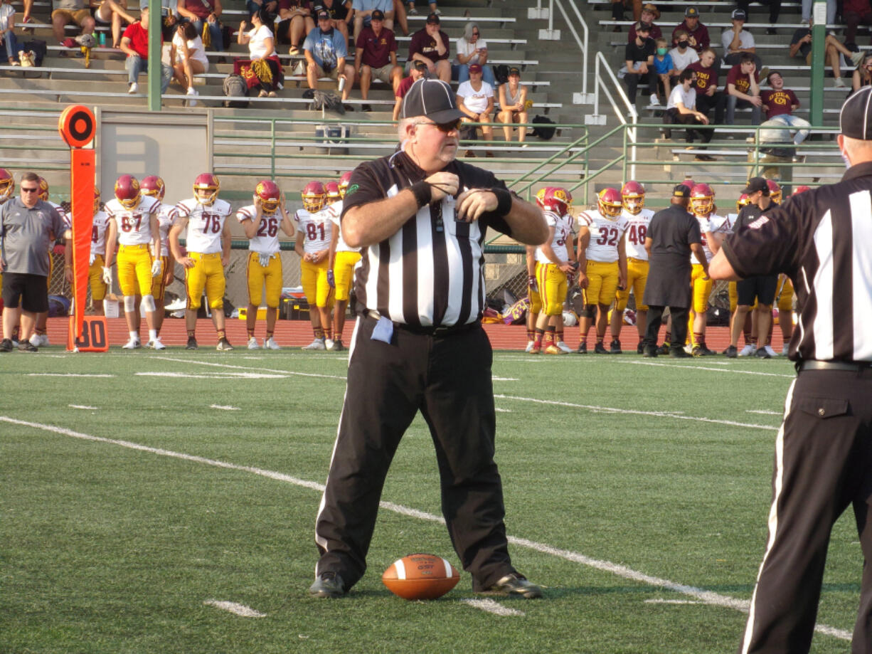 Chris Prothero of the Evergreen Football Officials Association stands over the ball during a timeout at the Union-O'Dea game on Sept. 3.