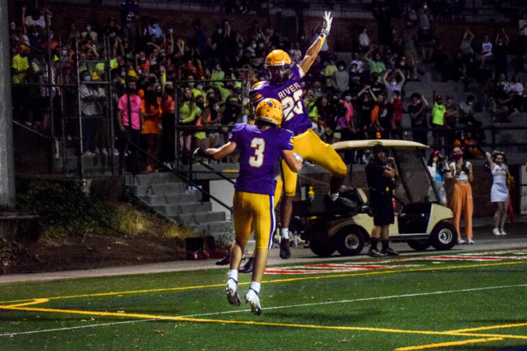 Columbia River's Victor Flores (23) and Thomas Blau (3) celebrate a Rapids touchdown run during River's 16-7 win over Woodland on Friday, Sept.
