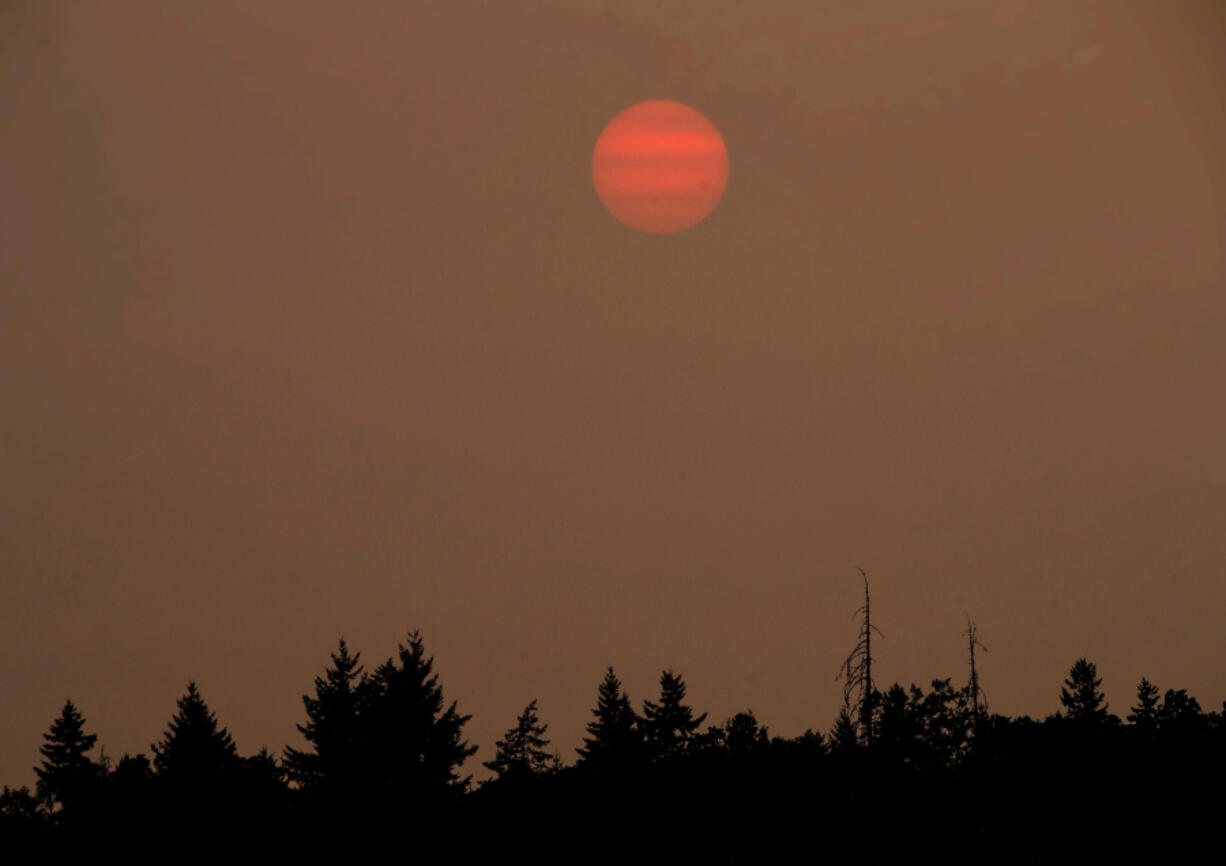 The sun sets Tuesday over Eugene, Ore., behind a blanket of thick smoke from wildfires burning in Oregon.