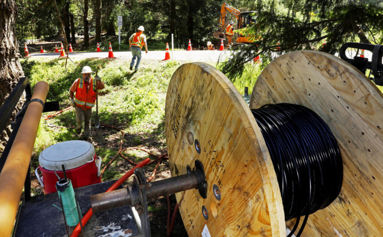 In this May 22, 2018 photo, a Whidbey Telecom crew prepares to thread fiber-optic cable under a road, which will deliver internet service to, in this case, a single home on Whidbey Island, in Freeland, Wash.