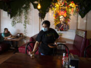 Vancouver resident Ashley Stevens enjoys lunch at 4 Caminos as Samantha Gomez cleans up after lunch customers on a recent Wednesday. Hispanic restaurants on Fourth Plain have had challenges with rising supply costs and labor shortages. At top, a sign at 4 Caminos lets customers know masks are required inside.