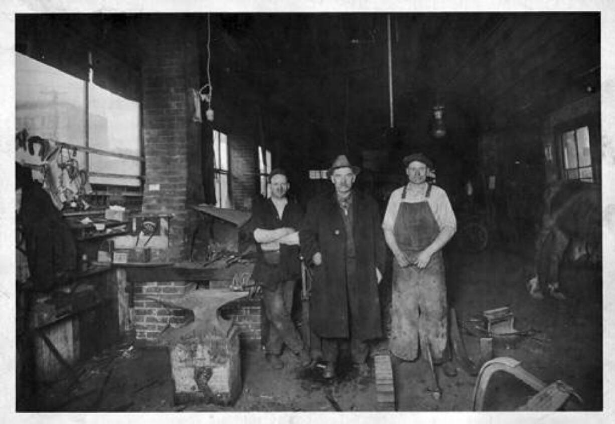 Three men inside Cooper's Blacksmith Shop at Fifth Street and Broadway in Vancouver interrupt their work to pose for a photo. From left to right: owner M.J. Cooper, J.E. Johnson and Heckman (first name unknown). In the horse-drawn era, blacksmiths forged tools, wheel rims and every tool they used. Blacksmith shops often attracted local men who chewed, smoked and exchanged gossip.