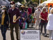 Guests walk past a sandwich board that alerts people to the COVID-19 guidelines recommended by the Vancouver Farmers Market on Saturday in downtown Vancouver.