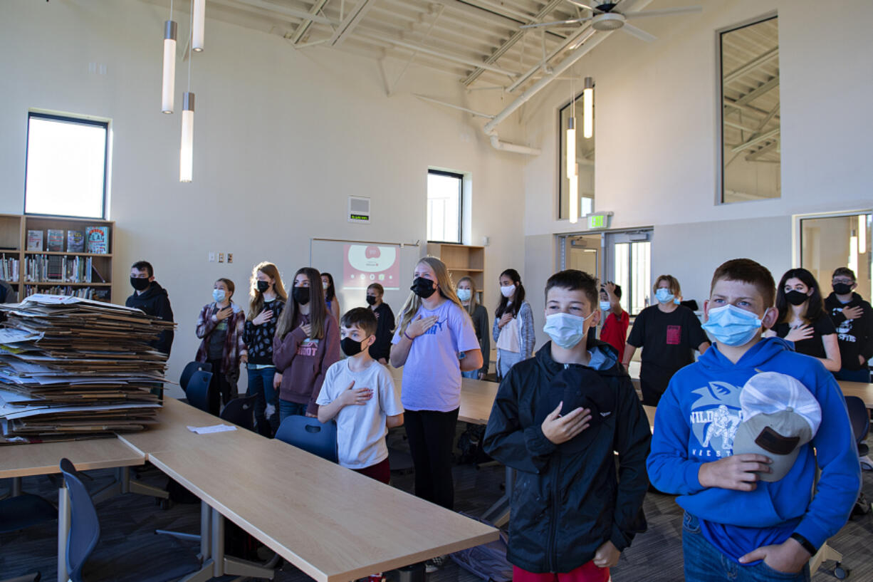 Seventh-grade students pause for the Pledge of Allegiance as they have their homeroom in the library, which is still being unpacked, at the new La Center Middle School. It's the first new school building in the district since the early 1990s.