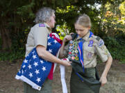 Helene Abbott, left, helps her daughter, Josephine Abbott, 14, as she prepares for a portrait at her home. Josephine has become the first female Eagle Scout in Southwest Washington.