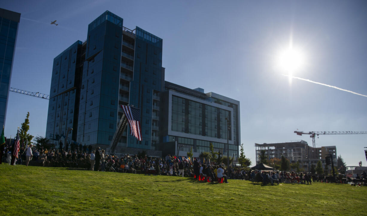 A plane flies overhead as hundreds gather for the 9/11 Remembrance Ceremony on Saturday at Waterfront Park in downtown Vancouver, marking 20 years since the terrorist attacks that hit the Pentagon and the Twin Towers of the World Trade Center.