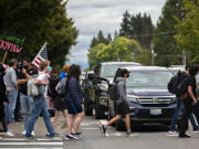 """Skyview High School students pass dueling protests outside their school Friday afternoon. Opposing groups expressed different points of view on the Vancouver Public School's injunction prohibiting protests, rallies or other demonstrations that """"disrupt educational services"""" within a mile of Vancouver schools."""