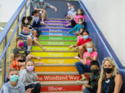 Leadership/SEL teacher Stacia Aschoff, far right, sits with her leadership class on the stairs of North Fork Elementary School in Woodland.