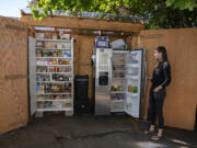 Gretta Anderson looks over contents of the free food pantry and fridge at her Vancouver home Monday afternoon. The Vancouver Free Fridge project is up to three fridges, but they're also being regulated by city codes over the structures, causing program leaders to start a petition.