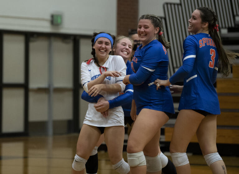 Ridgefield teammates swarm libero Emily Paul after her diving save kept the rally alive for a point the Spudders eventually won during a 2A Greater St. Helens League volleyball match on Tuesday, Sept. 21, 2021, at Columbia River High School. Ridgefield won 3-0.