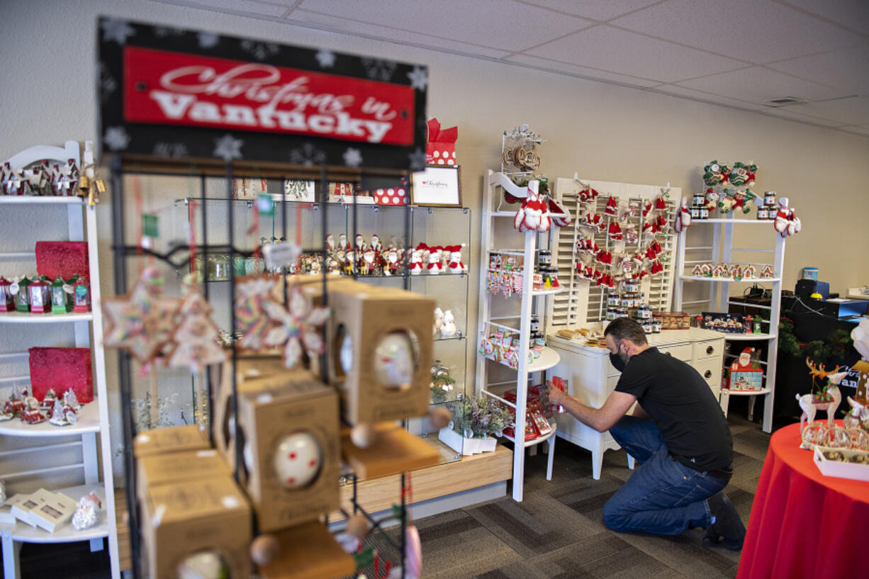 Manager Brandon Culp displays products on shelves while working at Christmas in Vantucky in Hazel Dell.