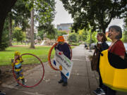 Ezra Little, 3, of Portland, from left, checks out a grown-up sized hula hoop while greeting Columbia Play Project performers Mary Sisson, Maureen Montague and Jeanne Bennett for a Give More 24! fundraiser Thursday morning at Esther Short Park in downtown Vancouver. The nonprofit set its fundraising goal at $10,000 and had received nearly $8,000 by late afternoon.