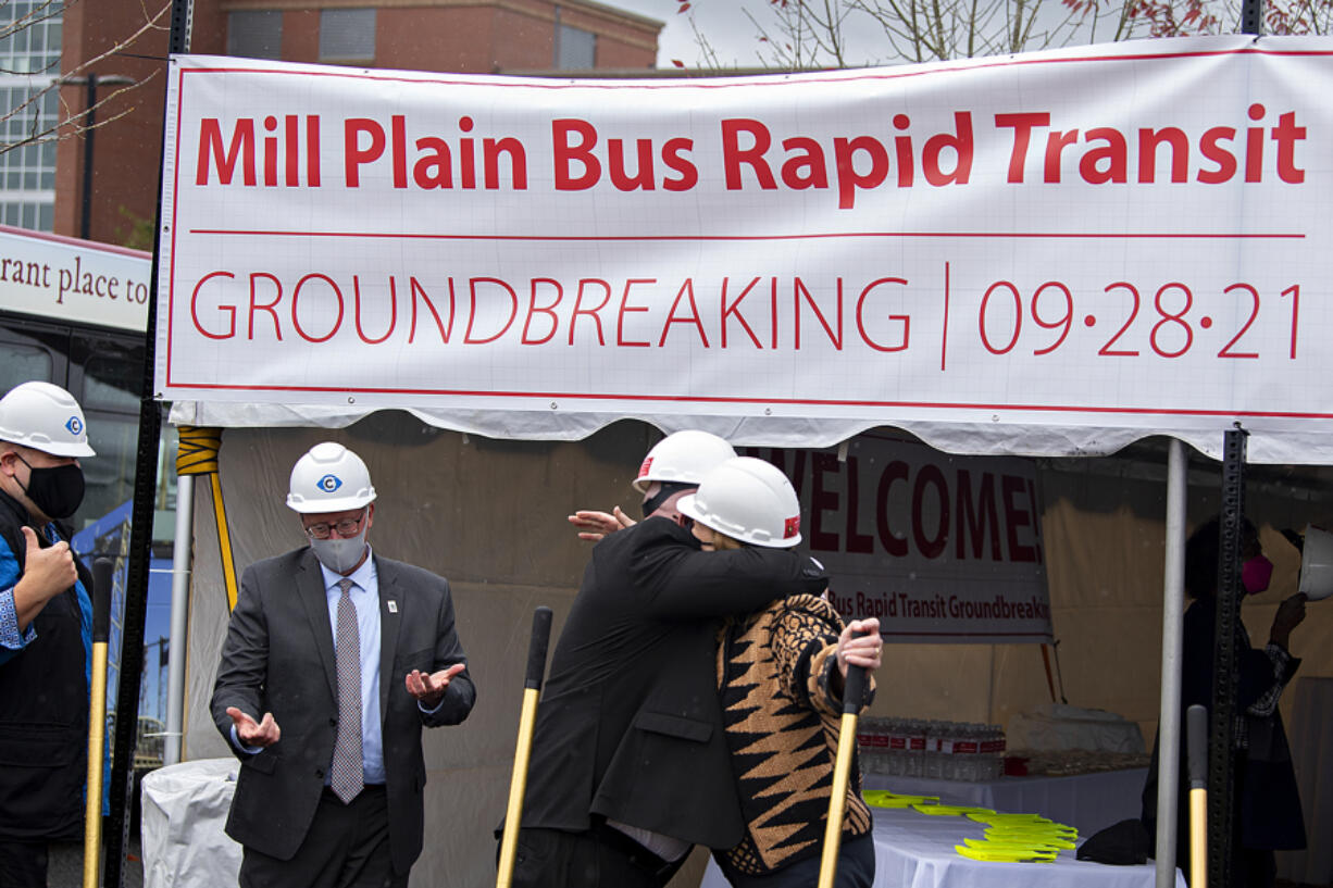 C-Tran CEO Shawn Donaghy, left center with shovel, embraces Vancouver Mayor Anne McEnerny-Ogle at the Clark College Columbia Tech Center campus as they celebrate the groundbreaking for the new Mill Plain Bus Rapid Transit line Tuesday afternoon.